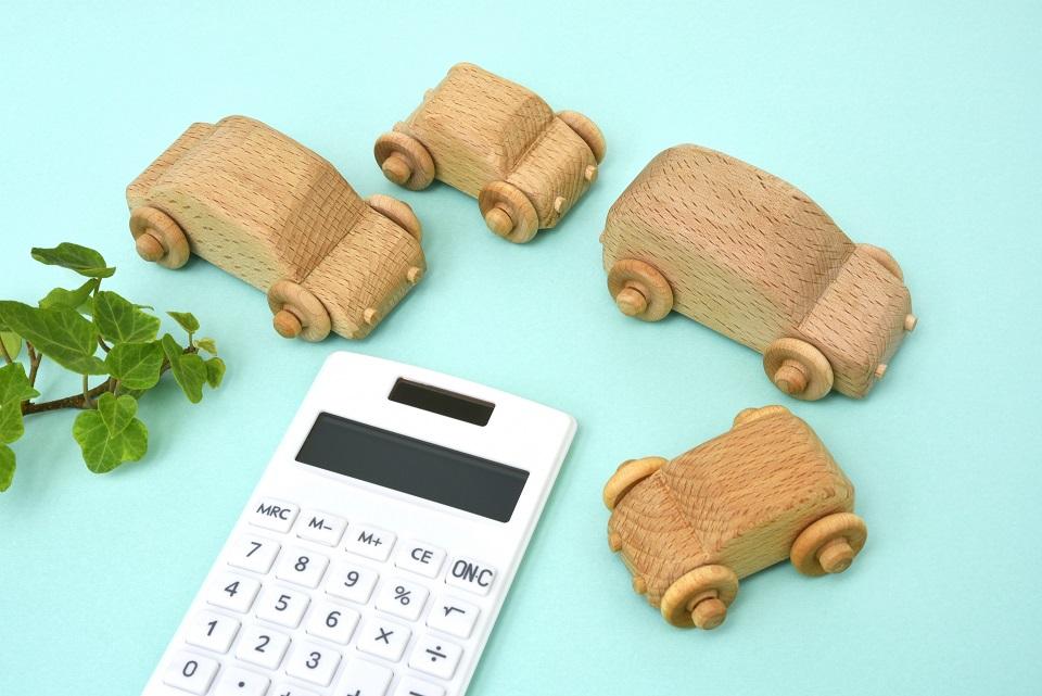電卓と木製の車のおもちゃ