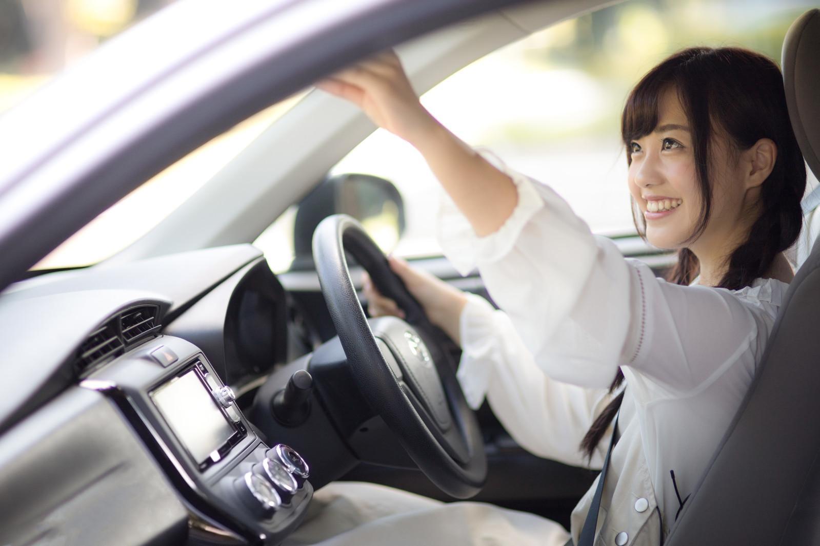 車中でバックミラーを確認する女性