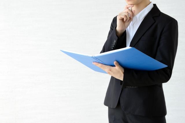 青いファイルを持って考える男性