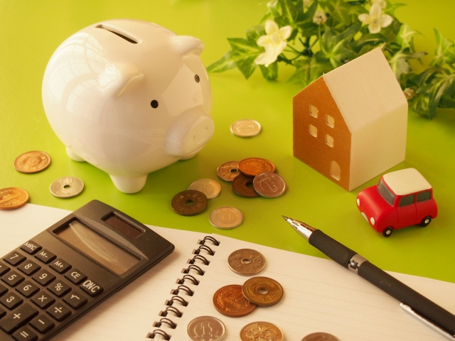 豚の貯金箱と電卓の周りに小銭が散りばめられている