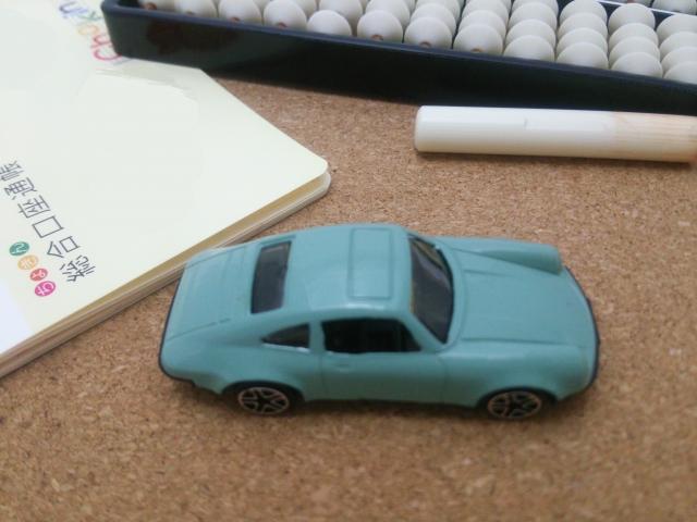 青い車の模型とそろばんと預金通帳