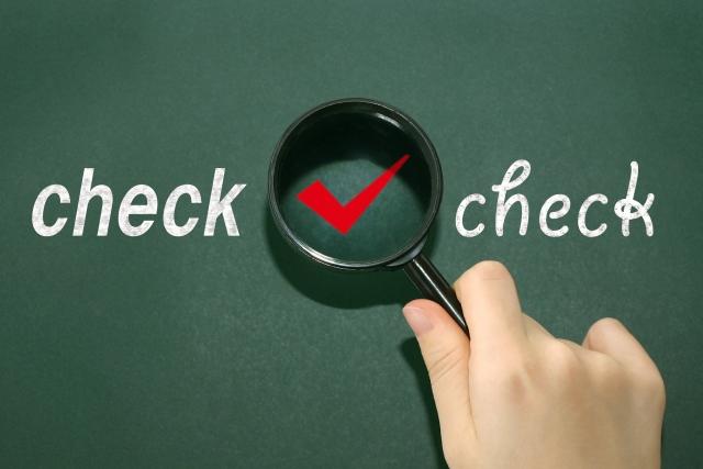 虫眼鏡で覗かれる黒板のチェックマークとcheckの文字