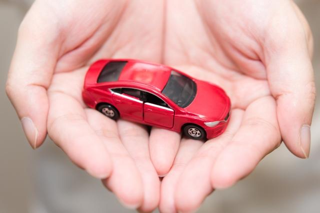 手のひらに乗せられた赤いおもちゃの車