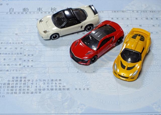 車検証の上に3台のおもちゃの車