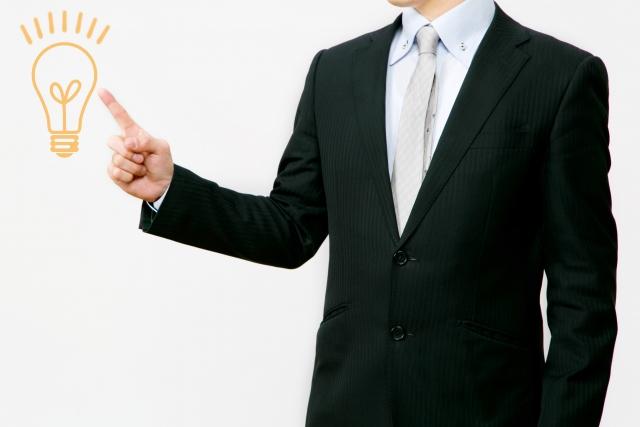 ひらめきマークを指さすスーツの男性