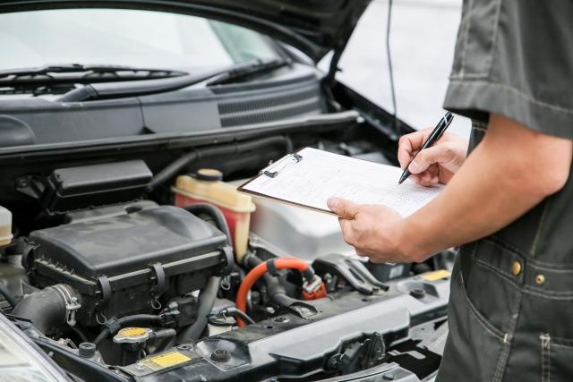 車のエンジンルームを点検する整備士