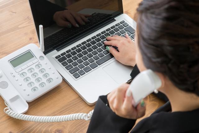 パソコンを打ちながら電話をする女性