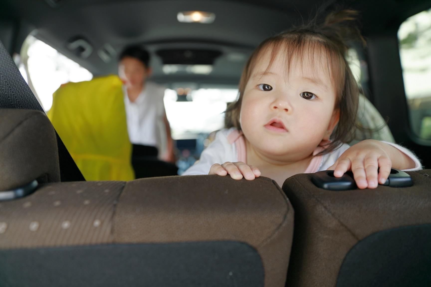 車の後部座席に乗る子供