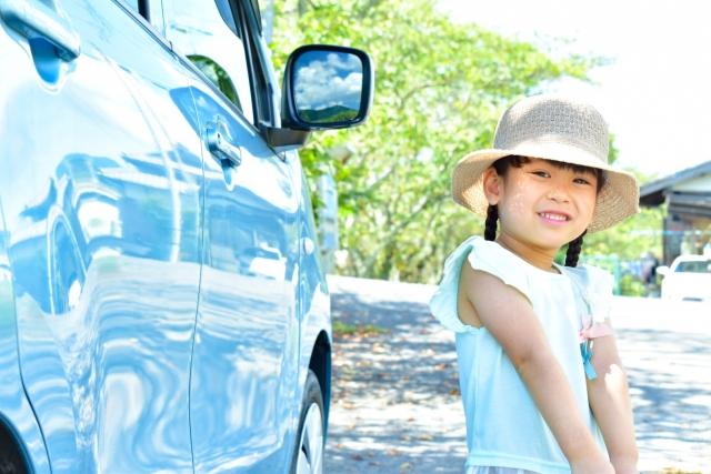 車の隣に立つ女の子