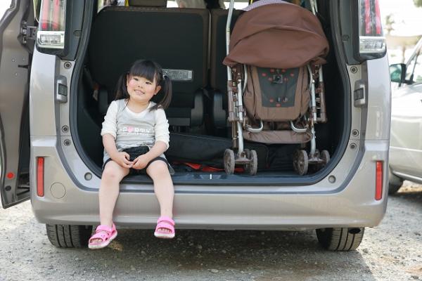 車のラゲッジスペースに座る子供