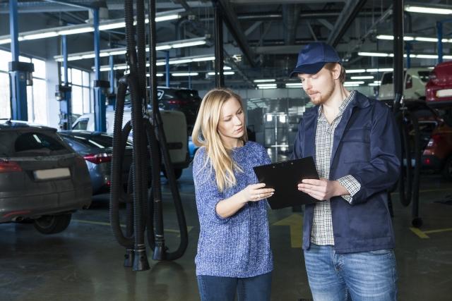 確認する自動車整備士と女性客