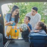 車から荷物を下ろす家族