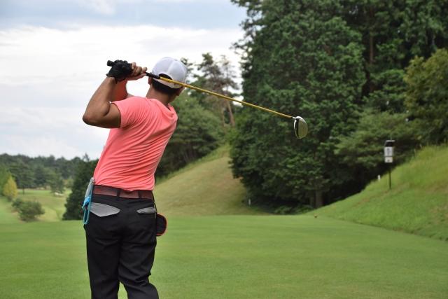 ゴルフのショットを打つ男性