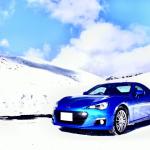 冬の山をドライブする青い車