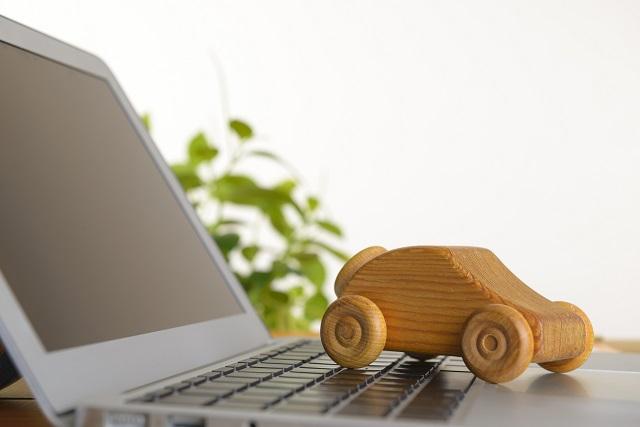 ノートパソコンと木製のミニカー