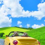 高原をドライブする黄色いオープンカー